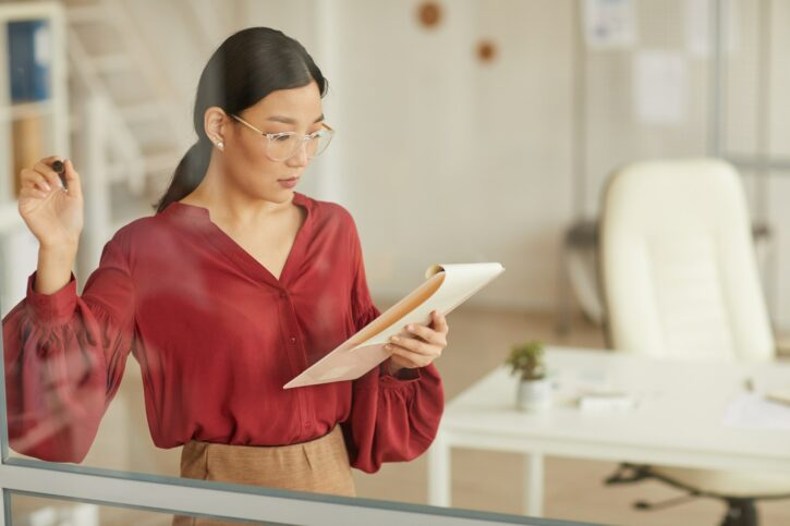 Asian Businesswoman Writing on Glass in Office