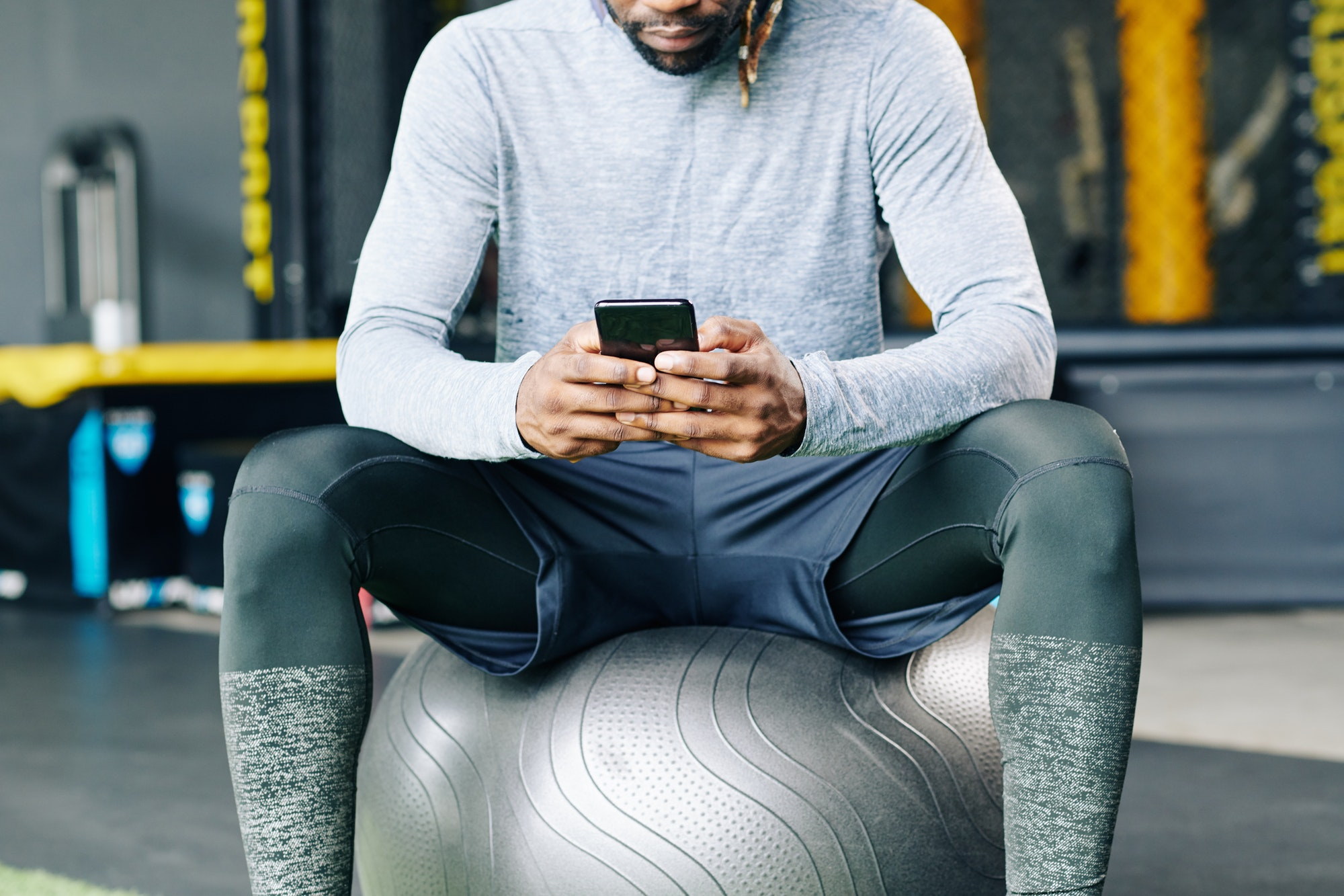 A man in a gym checks his mobile phone