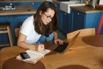 Image of serious nice woman working with laptop and writing