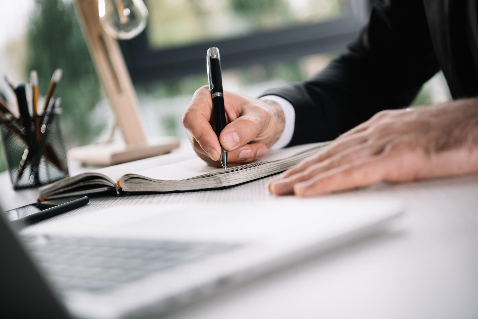 List of writing strategies: Man writing in notebook