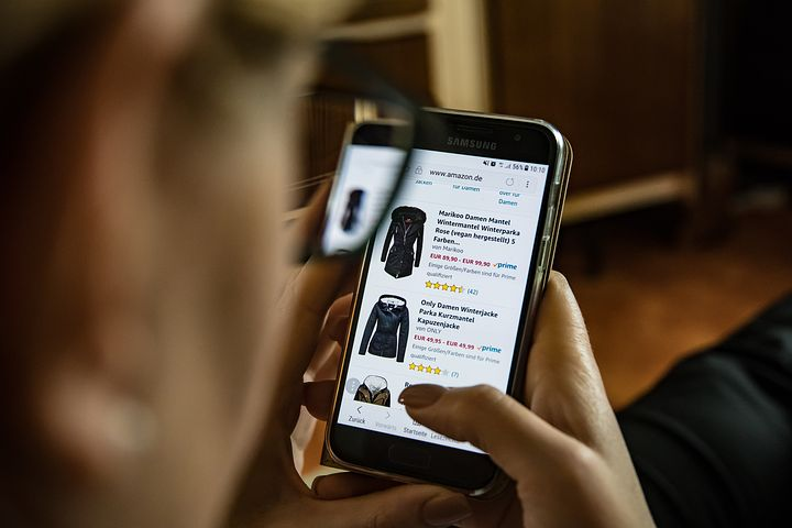 Sell clothes on Amazon: An out-of-focus person looks at clothing on Amazon on their mobile phone.