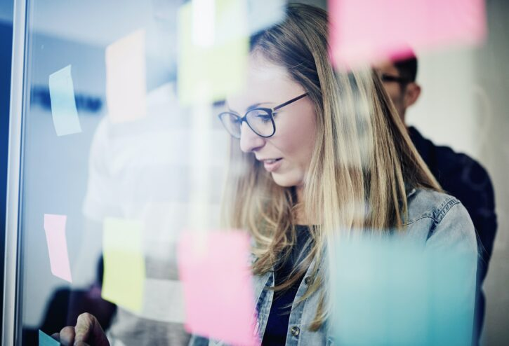 A businesswoman in front of a wall of sticky notes