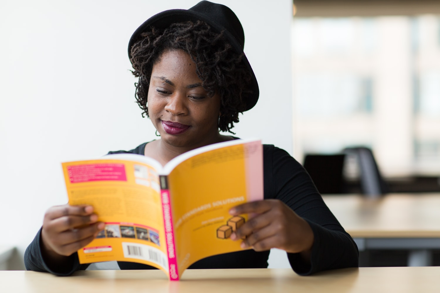 How to write a book title: a Black woman reads a book.