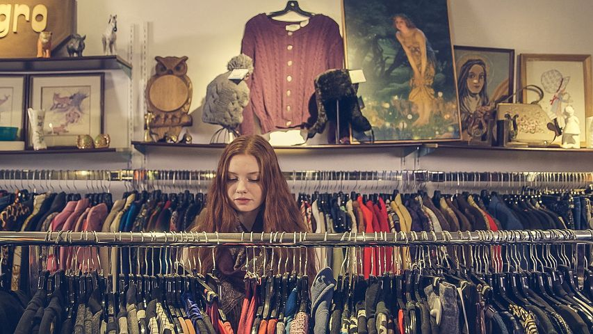 How to sell clothes on Amazon: A woman with long red hair looks at clothes in a clothing store.