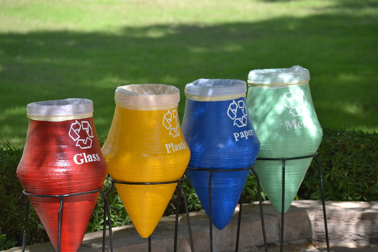 A photo showing four recycling bins of different colors.