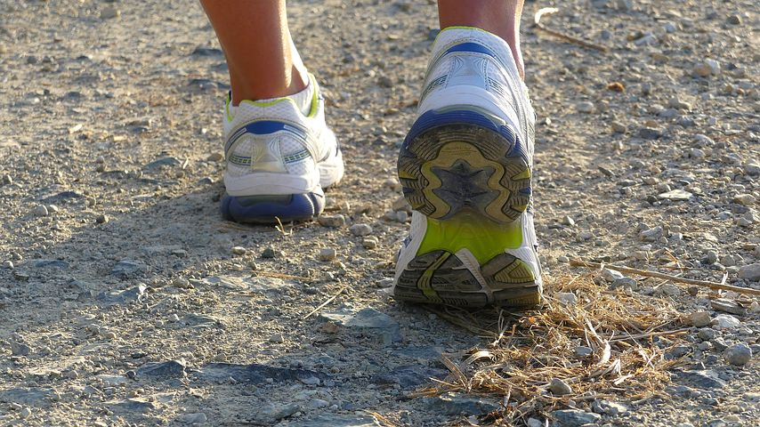 A person wearing white, green, and blue running shoes steps on a dirt road.