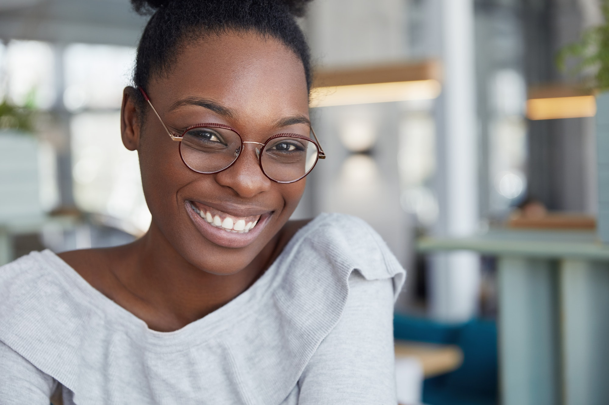 Best LinkedIn profile and cover photos: headshot of smiling Black female in round glasses