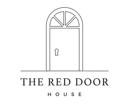 """A black and white image showing a door with a brand name: """"The Red Door House."""""""
