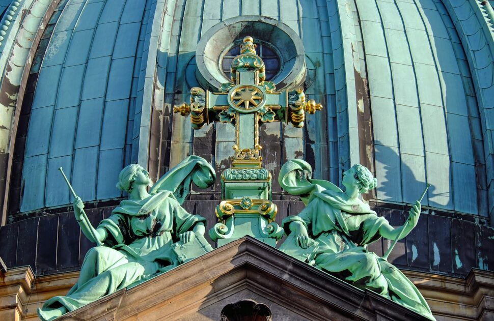 An image showing two statues by a cross at the Berlin Cathedral.