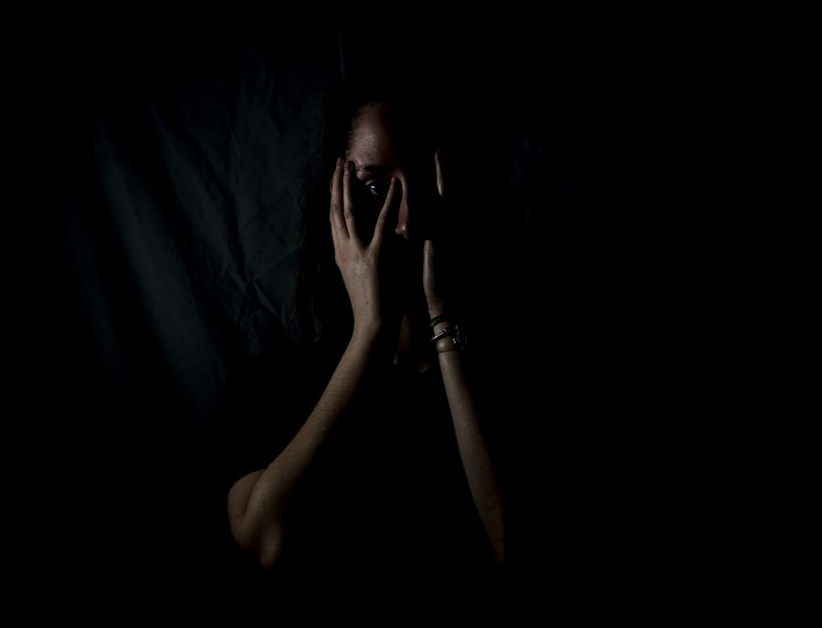 A woman peeks out from the shadows, looking scared.