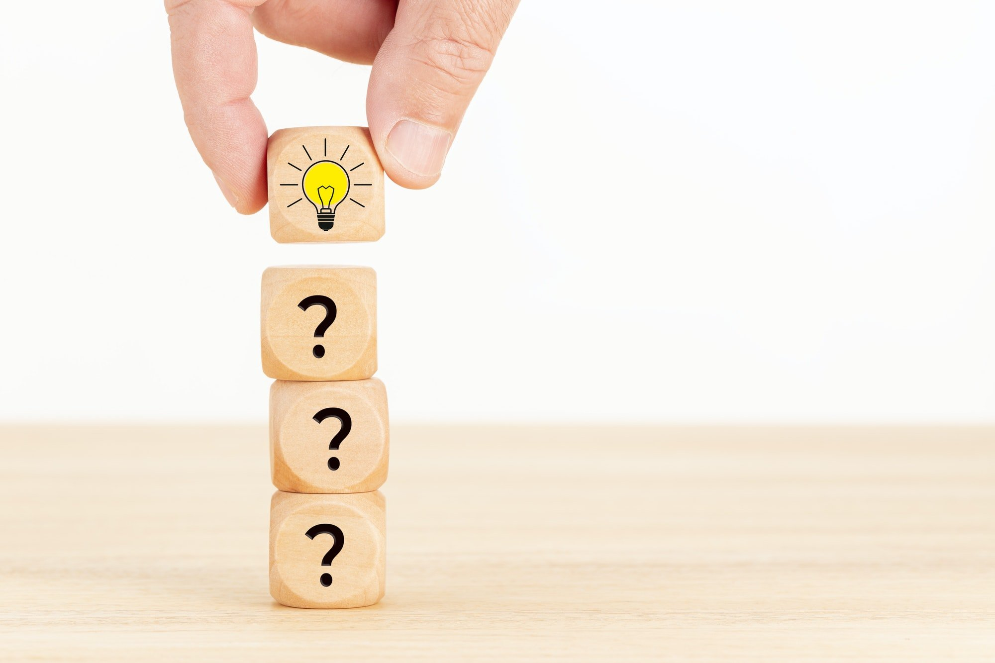 PickFu and MBA students: Stack of wooden cubes printed with question marks and a light bulb icon