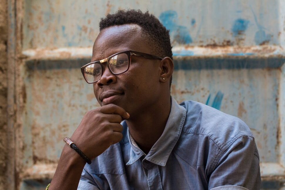 A Black man with glasses and a dress shirt looks thoughtfully at something.