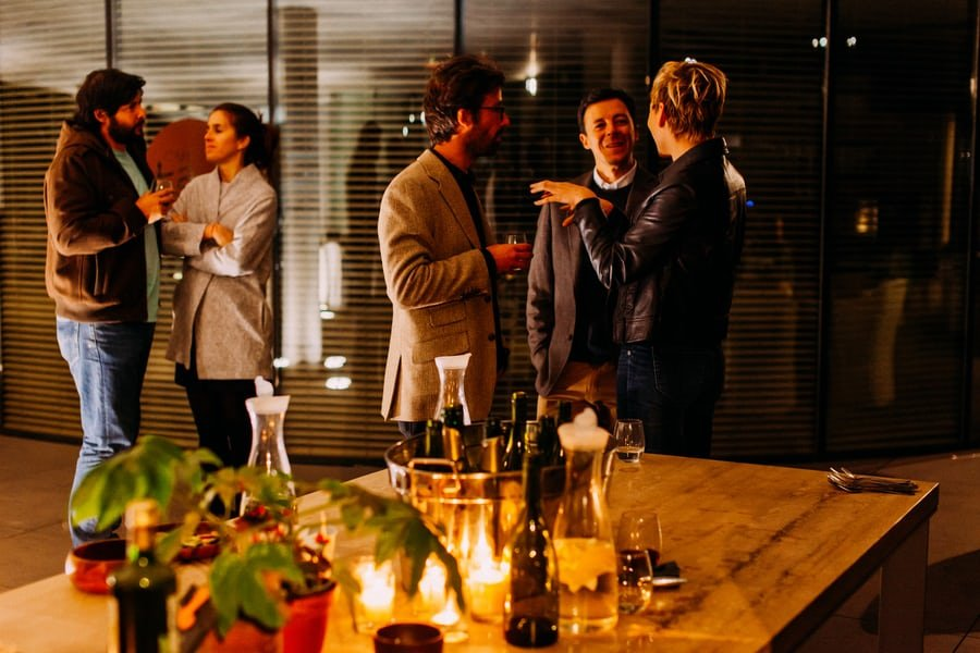 A group of people in business casual dress networks in the evening .
