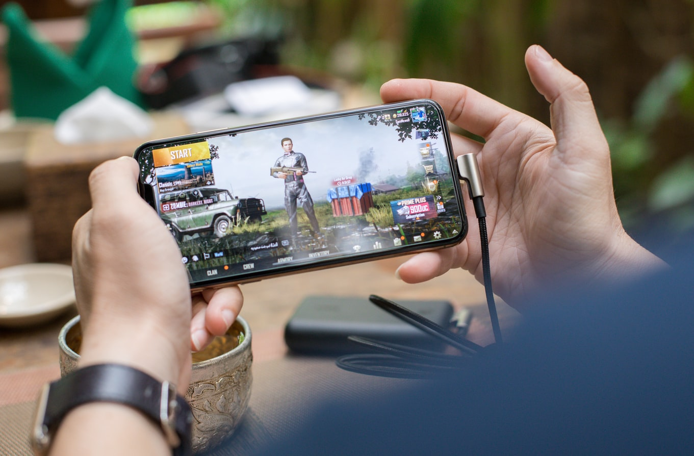 A person holds a mobile phone playing PUBG.