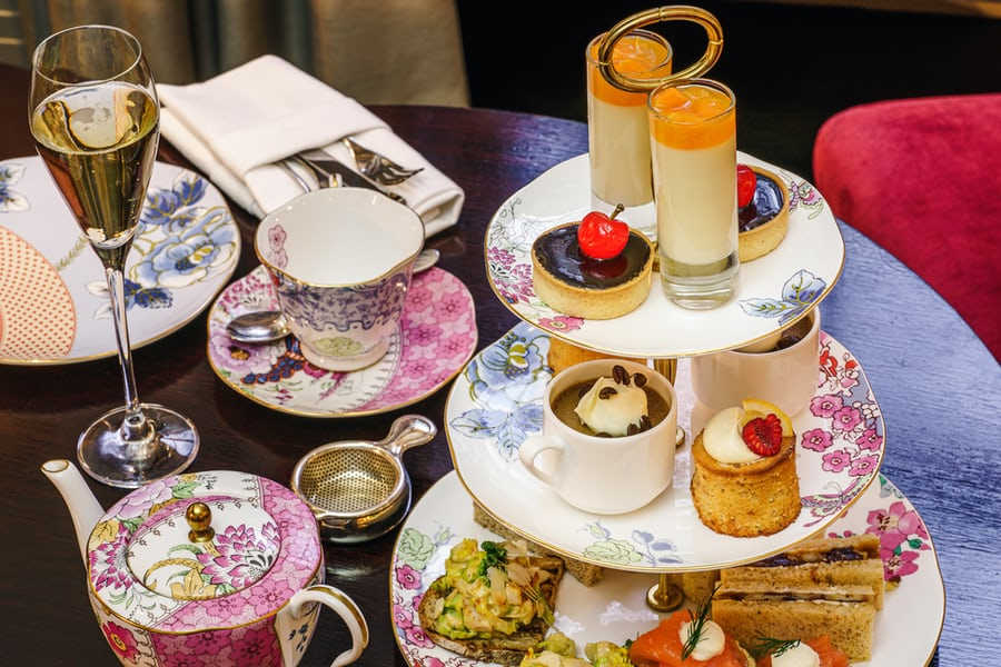 An image featuring tea, flowery pots and plates, and pastries for a London tea.