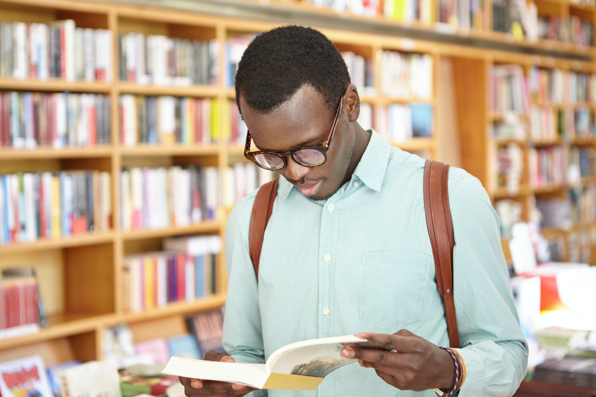 How to get reviews on Amazon: young man reading a book in a bookstore