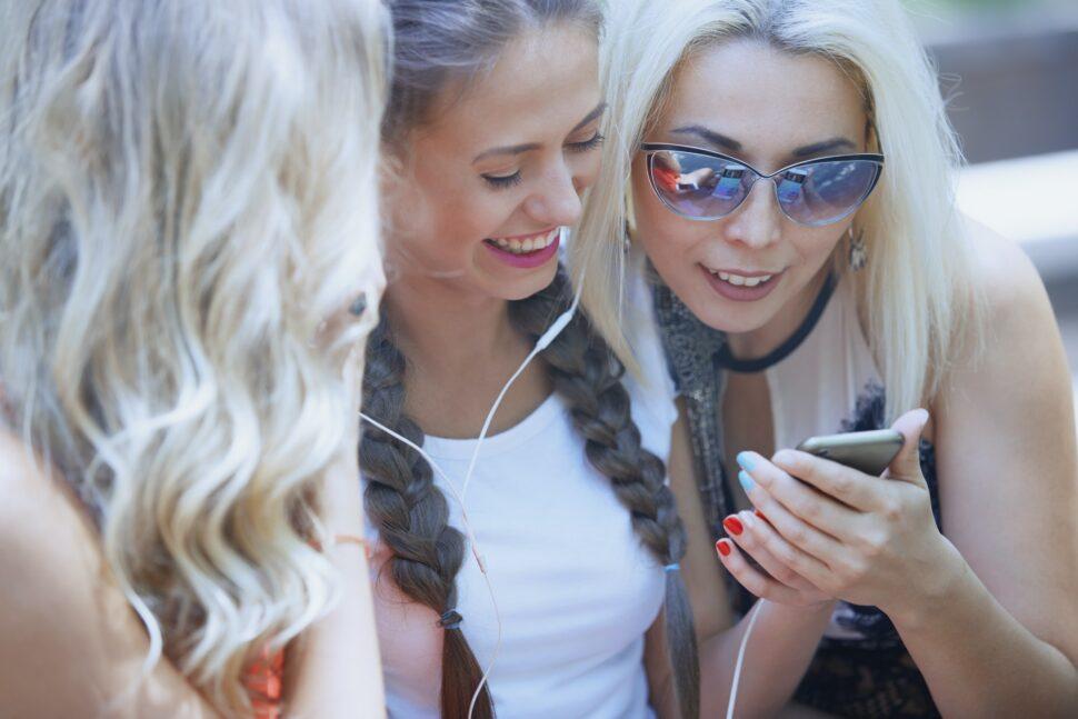 Girlfriends using smartphone and having fun in social media